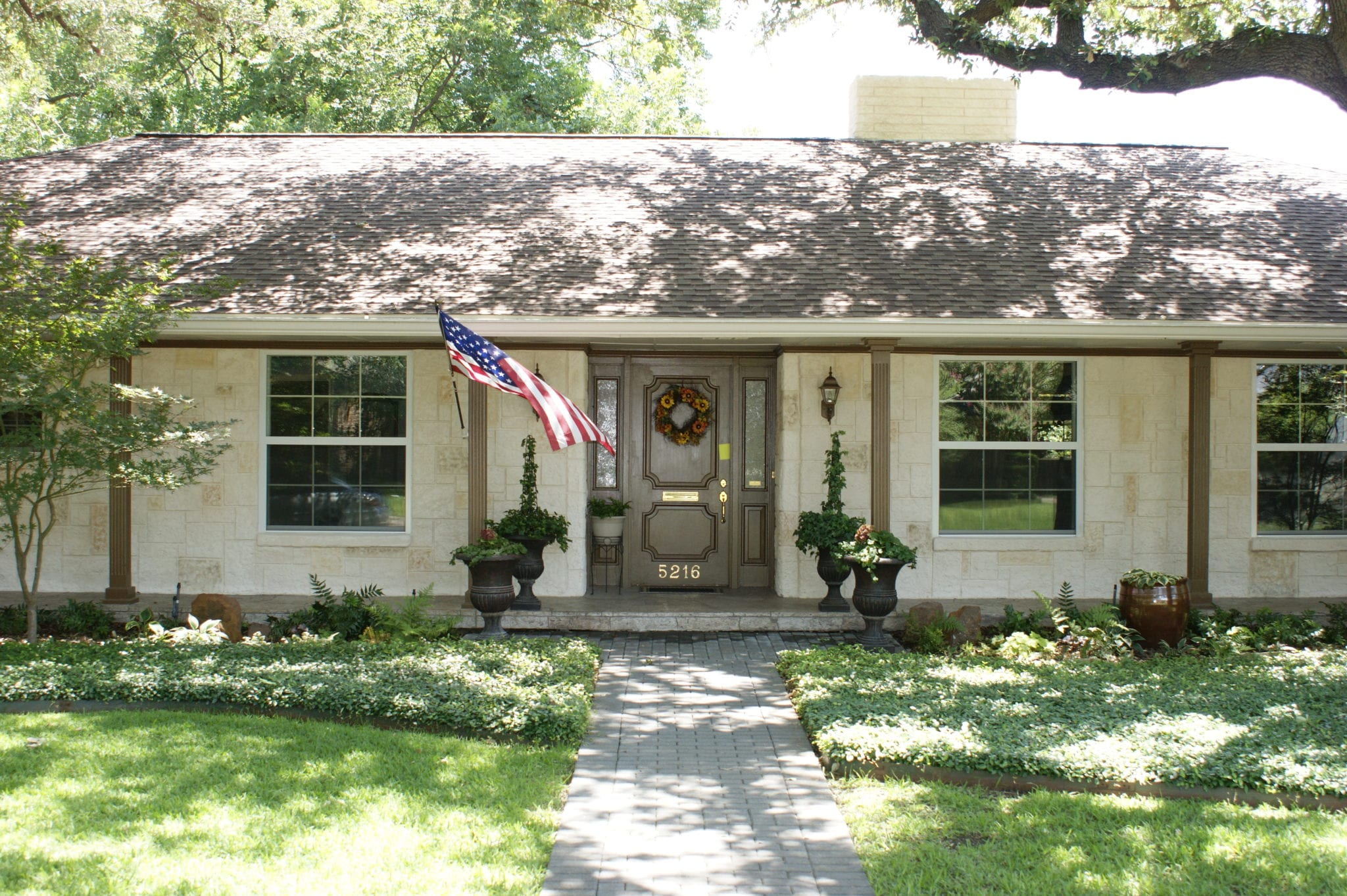 ranch style home, white limestone with american flag
